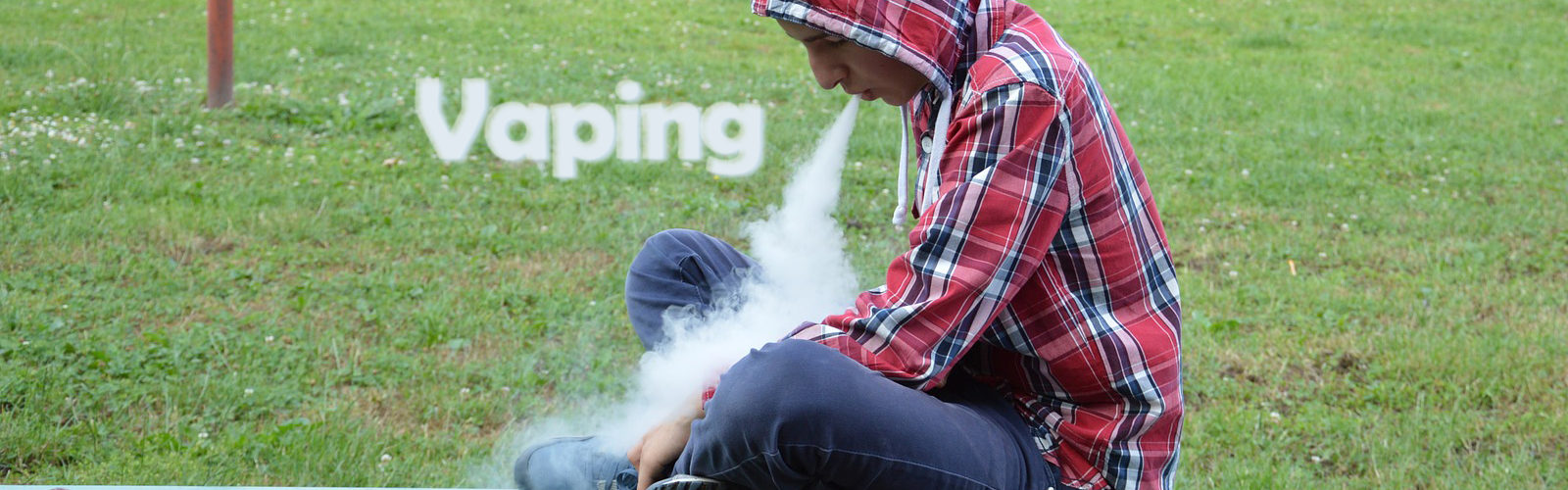 Man vaping on a park bench